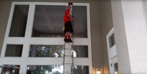 Professional window cleaners use stack ladders to clean windows